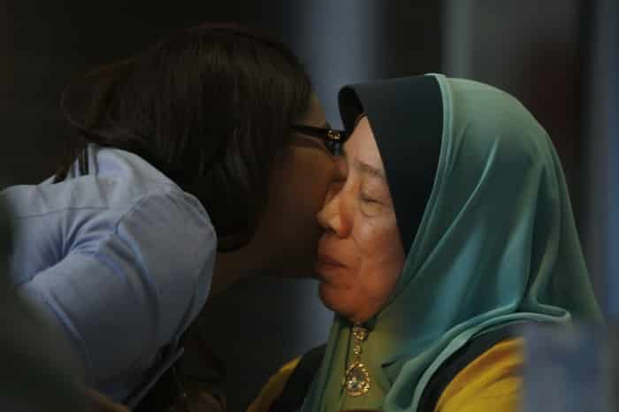 A journalist kisses the mother of a Malaysia Airlines flight MH370 passenger after an interview at the hotel where relatives of the passengers are staying in Putrajaya