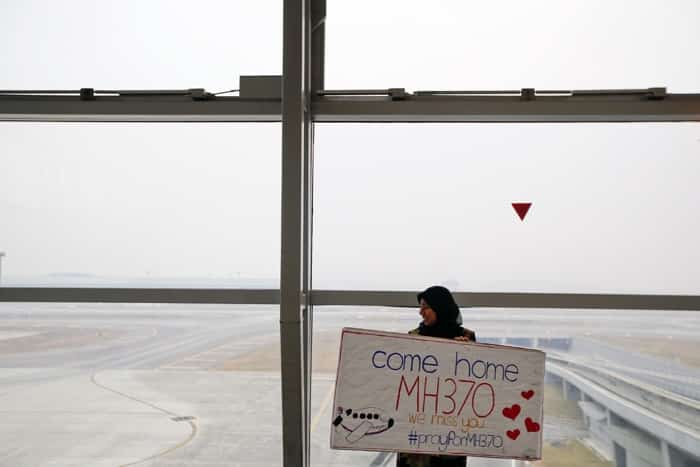 A woman holds a sign of support and hope for the passengers of the missing Malaysia Airlines flight MH370 she made and brought to the Kuala Lumpur International Airport