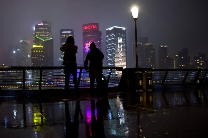 People stand on Bund across from illuminated buildings, on one of which is seen flight number MH370 of Malaysia Airlines plane that has gone missing, in Shanghai