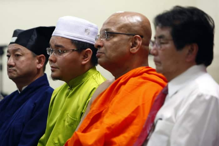 Representatives from different religions sit next to Malaysian Deputy Minister for Natural Resources and Environment Kurup during interfaith prayer for passengers and crew of missing Malaysia Airlines flight MH370, at Buddhist temple in Kuala Lumpur