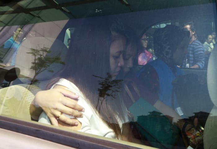 Family members of passengers onboard the missing Malaysia Airlines flight MH370 are seen in a car outside the hotel they are staying at, in Putrajaya