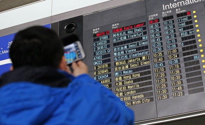A man takes pictures of a flight information board displaying the details of Malaysia Airlines flight MH370 (top, in red) at the Beijing Capital International Airport in Beijing